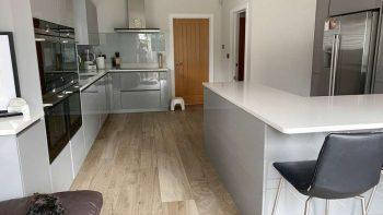 Beautiful Hacker Pearl Grey Gloss Handleless Kitchen with Composite Stone Worktops
